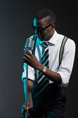 Retro Afro-Amerikaanse jazz-zangeres met microfoon. Het dragen van overhemd en stropdas en zonnebril. Studio-opname.