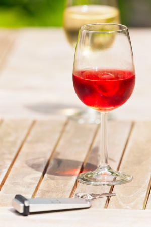 garden key: Glass of rose wine on wooden garden table with hotel key. Blurred white wine in background. Stock Photo