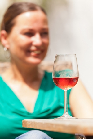 Glass of rose wine with blurred brunette smiling woman behind it. Wearing a green shirt. photo