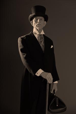 1900 stijl man met zwarte hoed en jas. Medicijnman in Dickens stijl. Houden city tas.