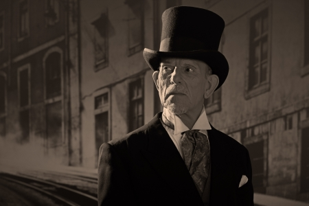 1900 style man wearing black hat and coat. Medicine man in Dickens style in night city street.