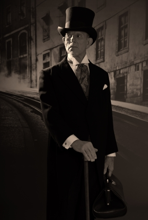 Man 1900 style wearing black hat and coat. Medicine man in Dickens style in night city street. Holding city bag. Stock Photo