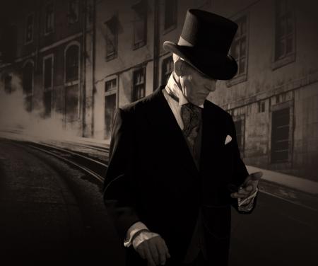 Man uit 1900 het dragen van zwarte hoed en jas. Medicijnman in Dickens stijl in de nacht stad straat. Het houden van een zakhorloge.