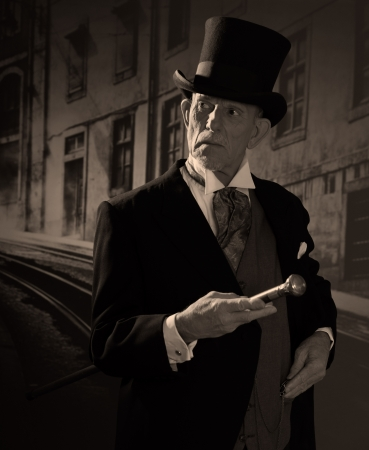 dickensian: Man 1900 style wearing black hat and coat. Dickens style in night city street. Stock Photo