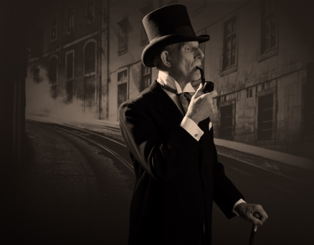 Man 1900 style smoking a pipe wearing black hat and coat. Dickens style in night city street. photo