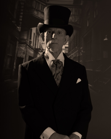 Senior man 1900 style wearing black hat and coat. Dickens style in night city street.