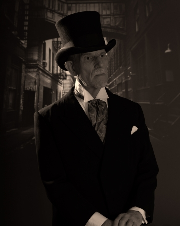 dickensian: Senior man 1900 style wearing black hat and coat. Dickens style in night city street.
