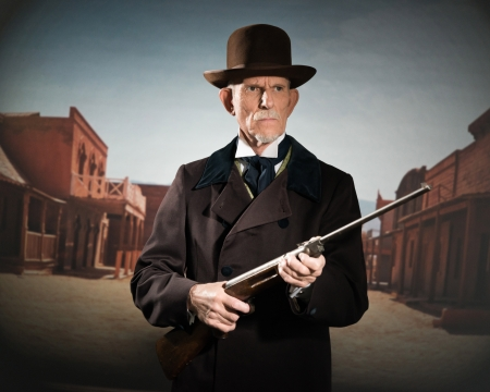 Senior western man wearing a brown hat and coat holding rifle. Standing in old small cowboy town.
