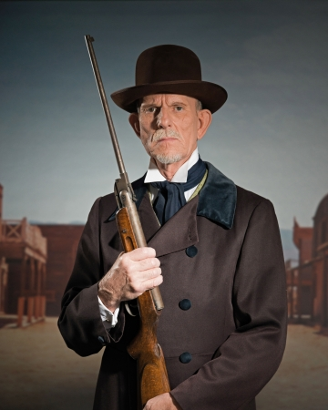 Senior western man wearing a brown hat and coat holding rifle. Standing in old small cowboy town. photo