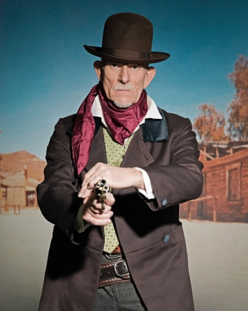 Senior western man wearing a brown hat and coat holding a revolver gun. Standing in old small cowboy town. Stock Photo
