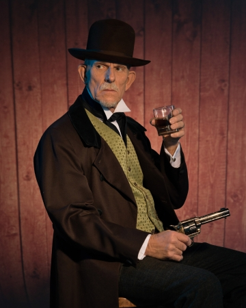 Senior alert western man wearing a brown hat and coat holding a revolver gun and whiskey. Sitting on chair in front of wooden wall in saloon. photo