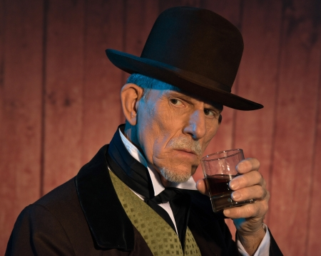 outlaws: Senior alert western man wearing a brown hat and coat holding a whiskey. In front of wooden wall in saloon.