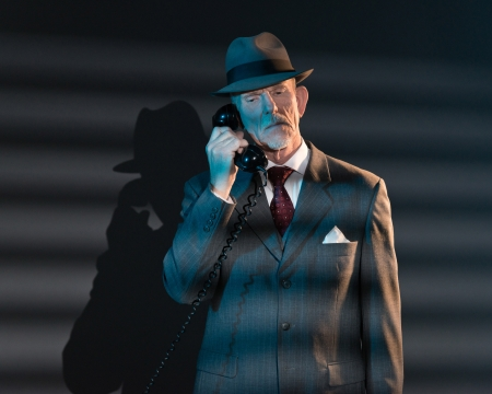 Retro detective man calling with vintage telephone at night in office. Lit by light through venetian blinds. photo