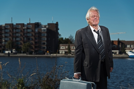 workless: Senior business man without a job and homeless on the street. Holding a suitcase. Dirty suit. Stock Photo
