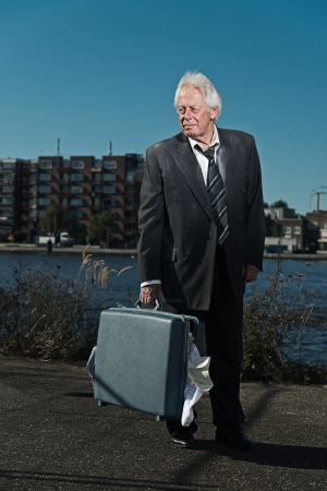 Senior business man without a job and homeless on the street. Holding a suitcase. Dirty suit. photo