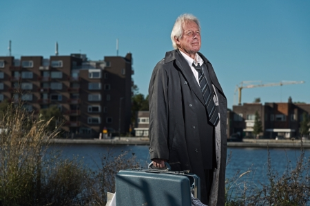 Senior business man without a job and homeless on the street. Holding a suitcase. Dirty suit and raincoat. photo