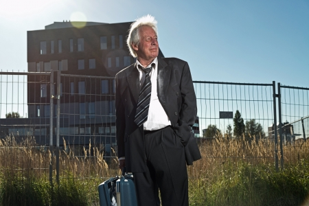 Depressed senior business man without a job standing in front of office building. Holding a suitcase. Wearing a dirty suit. photo