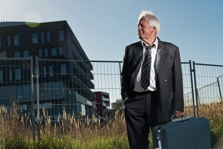 workless: Depressed senior business man without a job standing in front of office building. Holding a suitcase. Wearing a dirty suit.