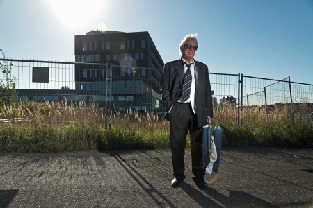 workless: Depressed senior business man with sunglasses without a job standing in front of office building. Holding a suitcase. Wearing a dirty suit.