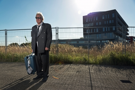Depressed senior business man with sunglasses without a job standing in front of office building. Holding a suitcase. Wearing a dirty suit. photo