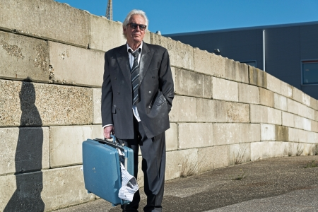 Depressed senior business man with sunglasses without a job and homeless on the street. Holding a suitcase. Wearing a dirty suit. photo