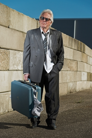 workless: Depressed senior business man with sunglasses without a job and homeless on the street. Holding a suitcase. Wearing a dirty suit.