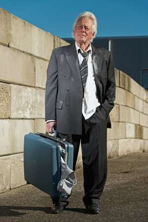 workless: Depressed senior business man without a job and homeless on the street. Holding a suitcase. Wearing a dirty suit. Stock Photo