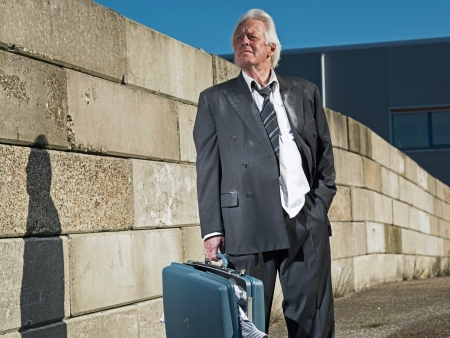 Depressed senior business man without a job and homeless on the street. Holding a suitcase. Wearing a dirty suit. photo