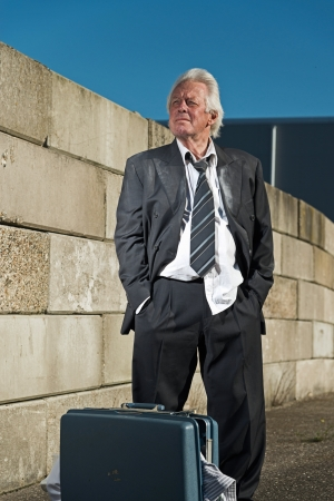 workless: Depressed senior business man with suitcase without a job and homeless on the street. Wearing a dirty suit.