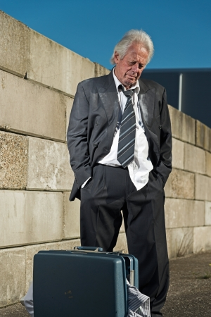 Depressed senior business man with suitcase without a job and homeless on the street. Wearing a dirty suit. photo