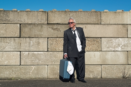workless: Lonely wandering depressed senior business man with sunglasses without a job and homeless on the street. Holding a suitcase. Wearing a dirty suit.