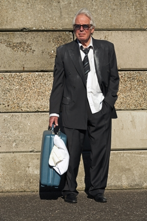 Lonely wandering depressed senior business man with sunglasses without a job and homeless on the street. Holding a suitcase. Wearing a dirty suit. photo