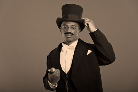 dickens: Retro afro american dickens scrooge man with mustache  Wearing black hat  Holding his hat  Stock Photo