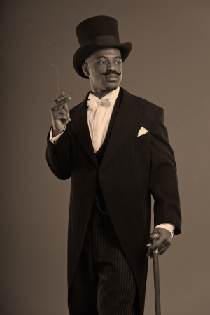 Retro afro american dickens scrooge man with mustache. Wearing black hat. Smoking a cigar. photo