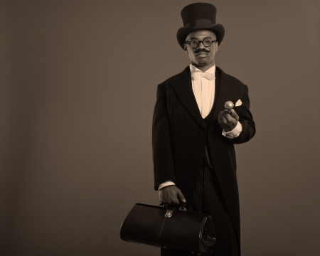 Retro afro american dickens scrooge man with mustache. Wearing black hat and glasses. Holding a city bag. photo