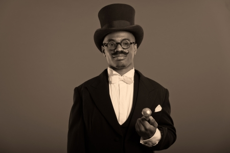 Retro afro american dickens scrooge man with mustache. Wearing black hat and glasses. Close-up portrait. photo