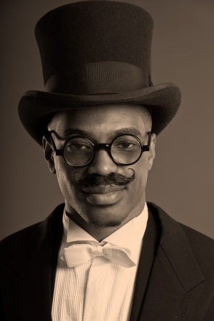 dickens: Retro afro american dickens scrooge man with mustache. Wearing black hat and glasses. Close-up portrait.