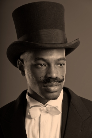 Retro afro american dickens scrooge man with mustache. Wearing black hat. Close-up portrait. photo