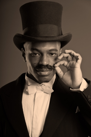 dickens: Retro afro american dickens scrooge man with mustache. Wearing black hat. Touching his mustache. Close-up portrait. Stock Photo