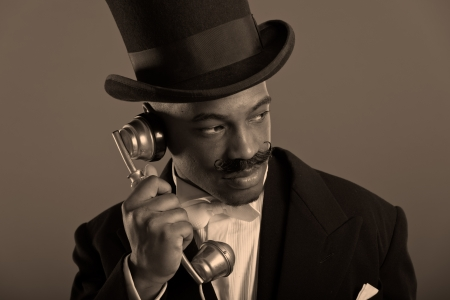 scrooge: Retro afro american dickens scrooge man with mustache calling with vintage phone  Wearing black hat  Close-up portrait