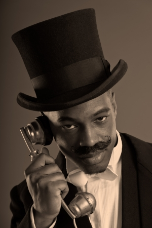 Retro afro american dickens scrooge man with mustache calling with vintage phone  Wearing black hat  Close-up portrait  photo