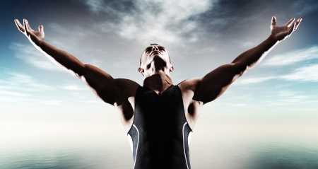 Muscled fitness triathlon athlete. Arms spread wide. Victory. Standing near lake. Stok Fotoğraf