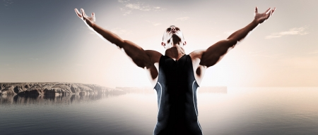 Muscled fitness triathlon athlete. Arms spread wide. Victory. Standing near lake. Stock Photo