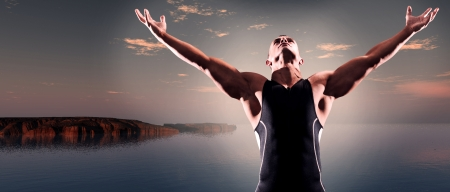 Muscled fitness triathlon athlete. Arms spread wide. Victory. Standing near lake at sunset. Stock Photo