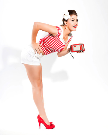 Sexy retro pin-up girl with radio and red lipstick wearing red striped shirt and white hot pants. Standing against white wall. photo