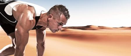 Extreme athlete runner man in starting position outdoor in desert on hot summer day