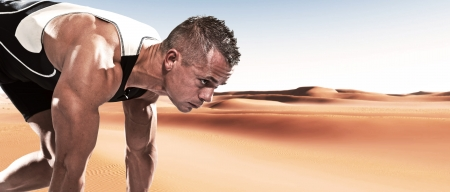 Extreme athlete runner man in starting position outdoor in desert on hot summer day