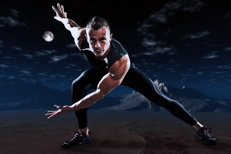 Triathlon runner man outdoor in night desert landscape. Extreme fitness sport. Standing in stretch position. photo