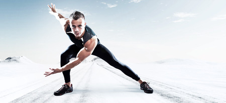 Triathlon runner man outdoor in winter snow landscape. Extreme fitness sport. Standing in stretch position. Warming up. Stock Photo