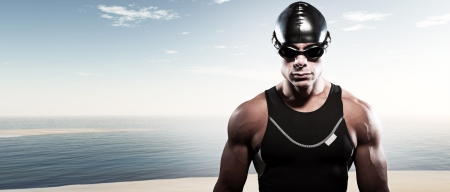 Swimmer triathlon muscled man with cap and glasses outdoor at a lake with blue cloudy sky. Extreme fitness sport. Stock Photo